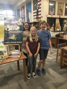 An author posing with 2 students next to a poster of her novel.