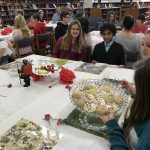 Students sitting down at a table with scones and fruit.