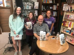Students and a teacher in a book store meeting an author.