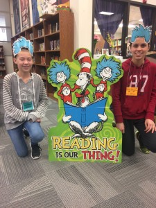 Students posing next to a Dr. Seuss Cat in the Hat stand.