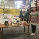 An author posing next to a display of her novels.