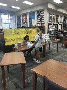 An author signing a book for a student.