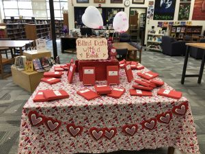 A blind date book display with books wrapped in red paper.